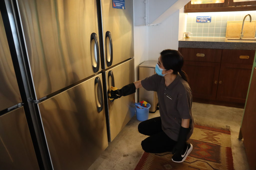 Magic Clean staff cleaning the fridge at the communal area